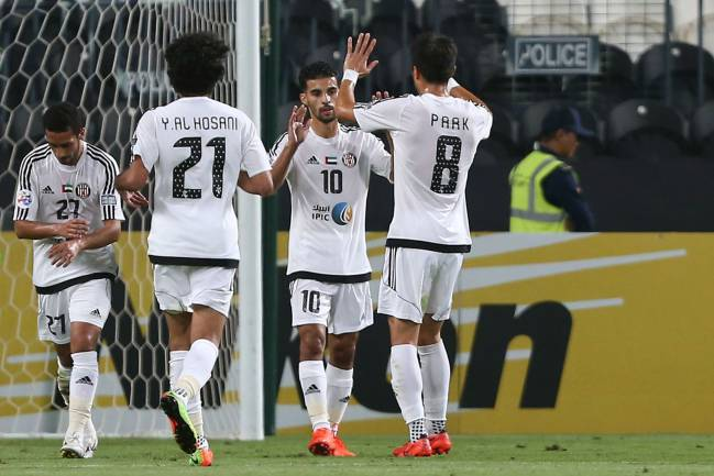 Al Jazira's Mbark Boussoufa is congratulated by team mates after scoring from the spot.