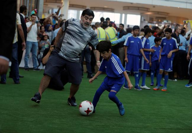 Argentine soccer legend Diego Maradona dodges ball, during a show game, with Bahraini local youth soccer club, at a mall, as part of the 67th FIFA Congress in Manama, Bahrain May 09, 2017.