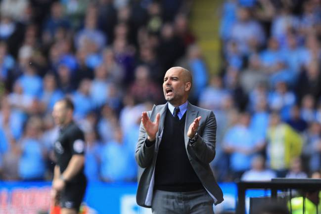 Guardiola, applauds his Manchester City players.