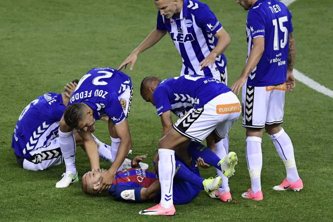 Barcelona's Argentinian defender Javier Mascherano is helped by Deportivo Alaves players.