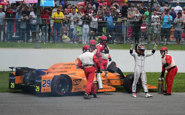 Fernando Alonso leaves his car after his engine failed at the 101st Indianapolis 500.