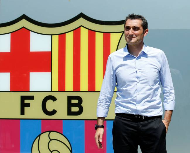 Coach Ernesto Valverde poses in front of FC Barcelona's giant logo at their offices at Camp Nou Stadium in Barcelona