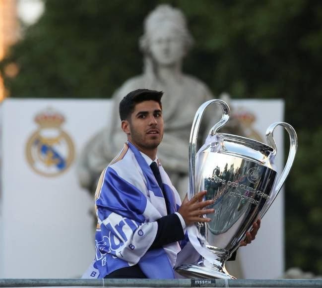 Real Madrid's Marco Asensio holds trophy as he celebrates Champions League at Cibeles Fountain.