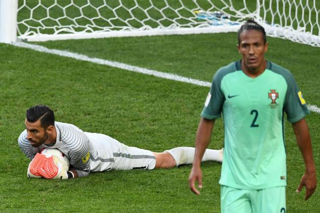 Portugal's goalkeeper Rui Patricio stops the ball next to Portugal's defender Bruno Alves during