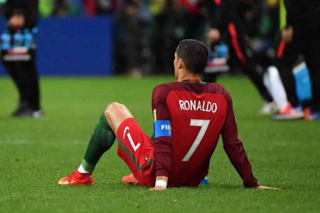 Portugal's forward Cristiano Ronaldo sits on the pitch during the 2017 Confederations Cup semi-final football match between Portugal and Chile
