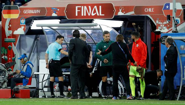 Referee Milorad Mazic consults with the VAR before showing Chile's Gonzalo Jara a yellow card.