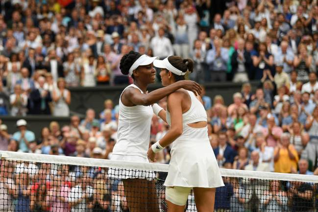 A victorious Garbine Muguruza of Spain is embraced by Venus Williams