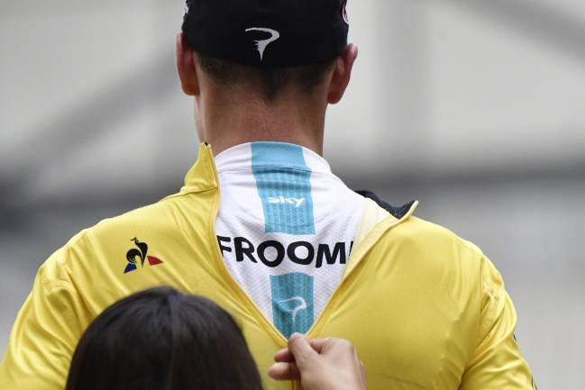 A hostess zips up the overall leader yellow jersey on Great Britain's Christopher Froome.