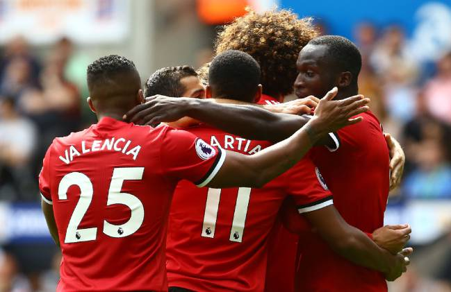 Manchester United's Belgian striker Romelu Lukaku (R) celebrates with teammates scoring the team's second goal