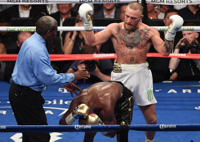 Floyd Mayweather Jr. reacts to a punch from Conor McGregor during their super welterweight boxing match