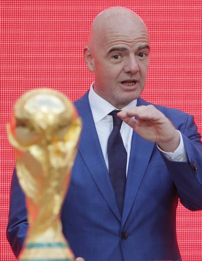FIFA President Gianni Infantino gestures as he stands behind the trophy at the FIFA World Cup Trophy Tour kick-off ceremony