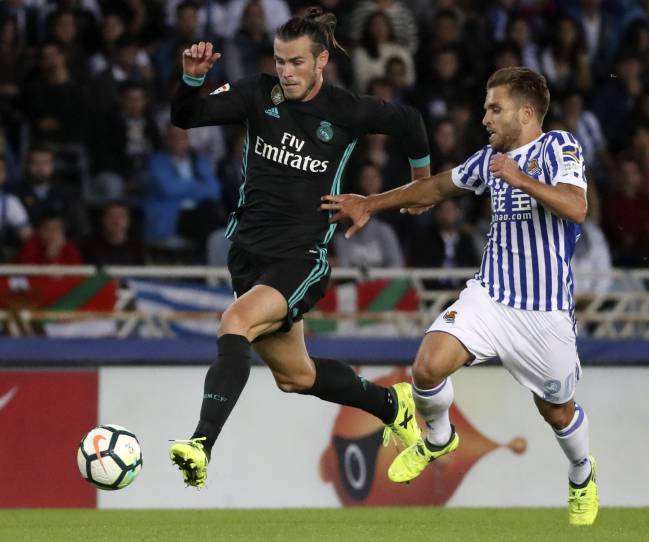 Real Madrid's Gareth Bale outsprints Kévin Rodrigues in his run towards Real Sociedad's goal.