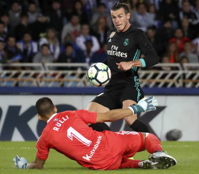Bale lifts the ball superbly over the onrushing Rulli.