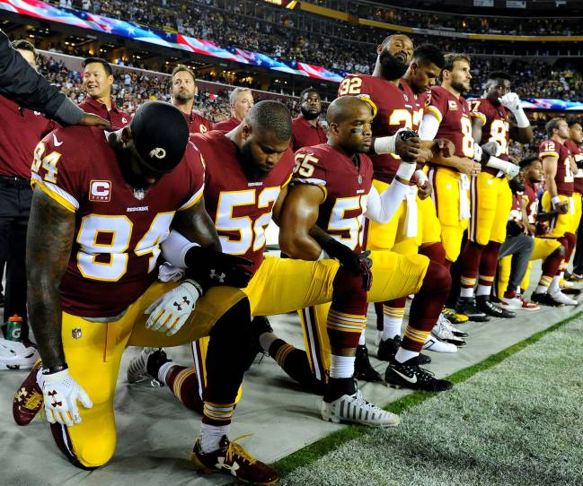 Washington Redskins tight end Niles Paul and linebacker Ryan Anderson and Washington Redskins linebacker Chris Carter kneel with teammates