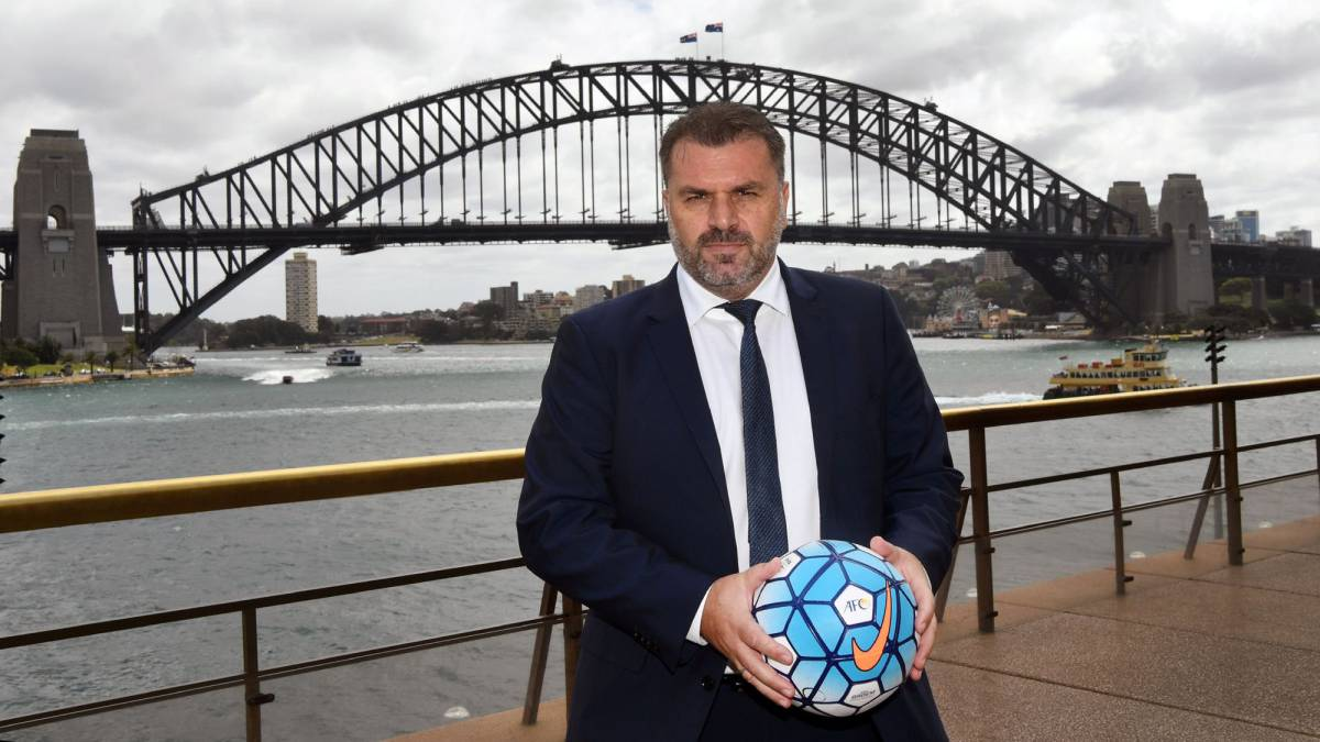 Australia's football coach Ange Postecoglou holds a football as he poses for a photo in front of the Sydney Harbour Bridge