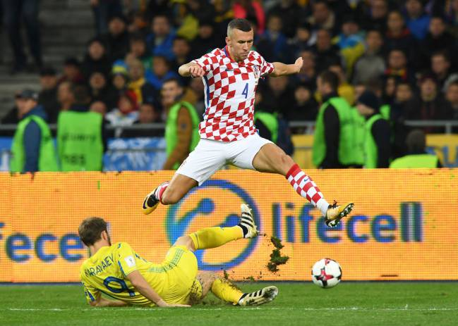 Croatia's Ivan Perisic jumps over Ukraine's Oleksandr Karavayev.