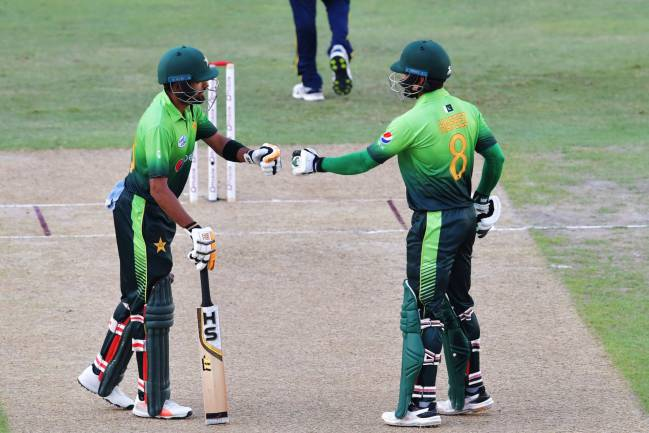 Pakistan's Babar Azam (L) and Muhammad Hafeez gesture during the first one day international (ODI) cricket match between Sri Lanka and Pakistan.