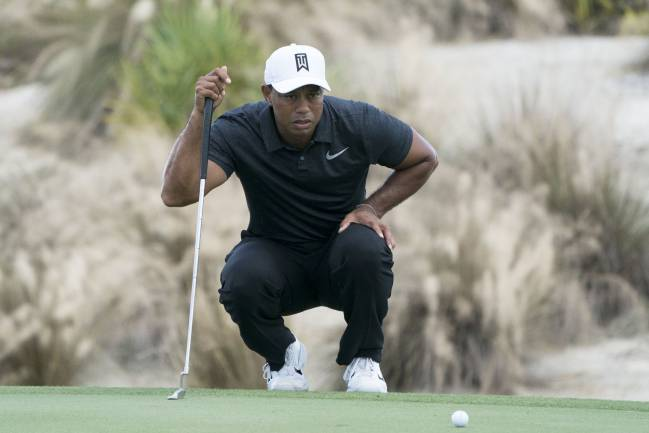 Tiger Woods lines up his putt on the second hole during the first round of the Hero World Challenge golf tournament at Albany.