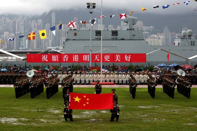 "People's Liberation Army Navy soldiers take part in a parade with a banner ""Wishing Hong Kong a Better Tomorrow"", during an open day at a naval base in Hong Kong, China July 8, 2017."