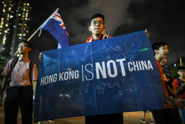 A football fan makes his feelings known while another waves the old British colonial flag after a match in Hong Kong.