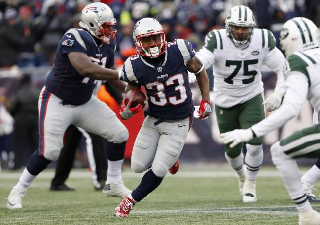 New England Patriots running back Dion Lewis (33) runs through the New York Jets defense during the second half of New England's 26-6 win at Gillette Stadium.
