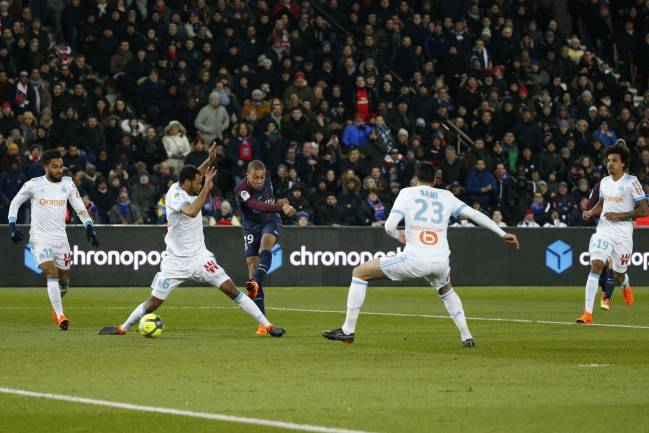 Paris Saint-Germain's French forward Kylian Mbappe shoots and scores despite Marseille's Rolando and Adil Rami's best attempts.