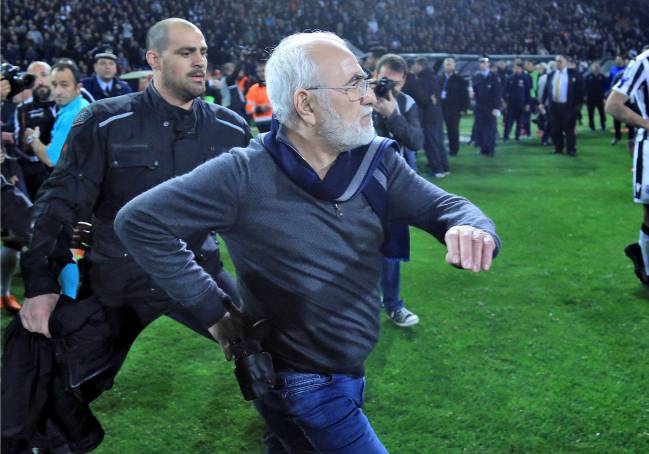 Russian-born Greek businessman and owner of PAOK Salonika, Ivan Savvides, pictured with what appears to be a gun in a holster, enters the pitch.