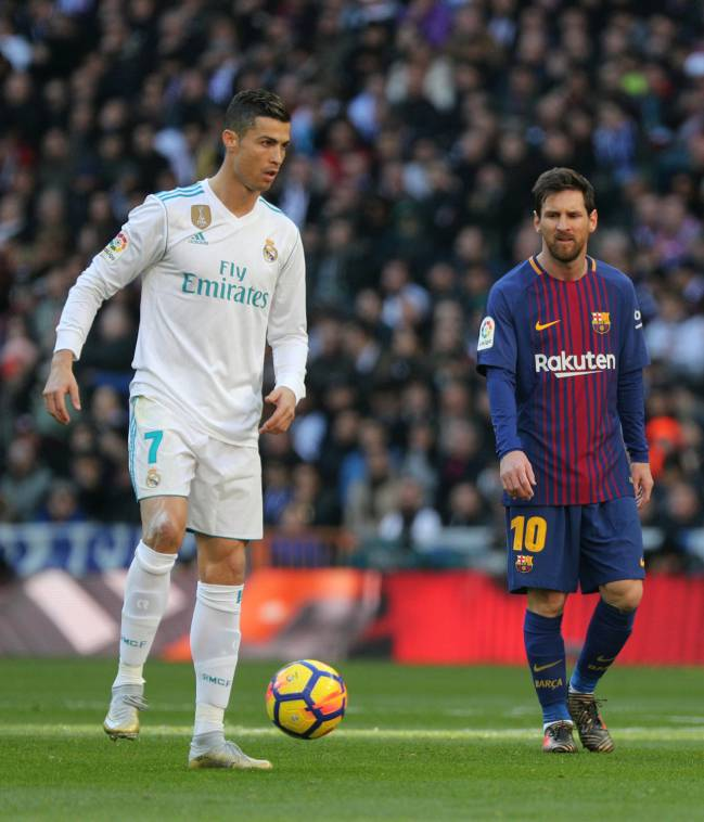 Real Madrid's Cristiano Ronaldo in action with Barcelona's Lionel Messi.