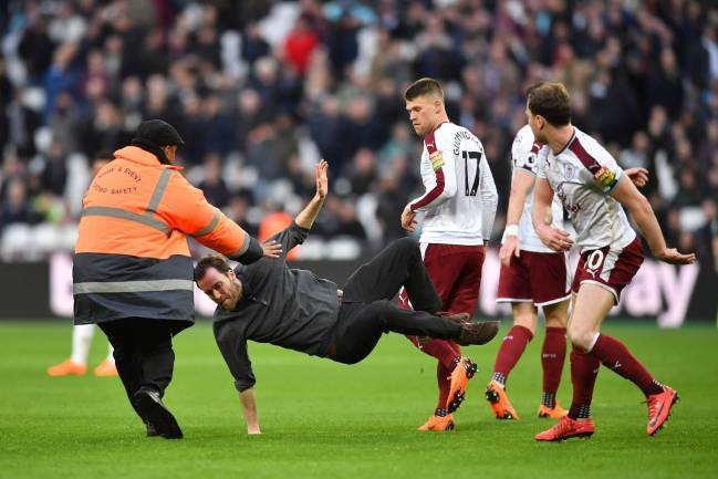 Burnley's English striker Ashley Barnes trips up a pitch invader during the English Premier League football match against West Ham United.