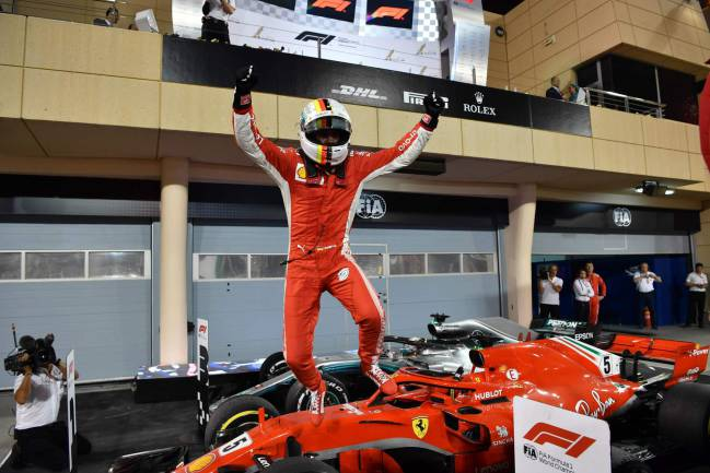 Ferrari's German driver Sebastian Vettel jumps out of his car after winning the Bahrain Formula One Grand Prix at the Sakhir circuit in Manama on April 8, 2018.