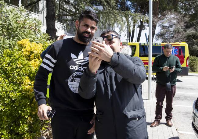 Forget the docs, have a selfie with me | Diego Costa smiles for the congregated fans outside the medical facility.