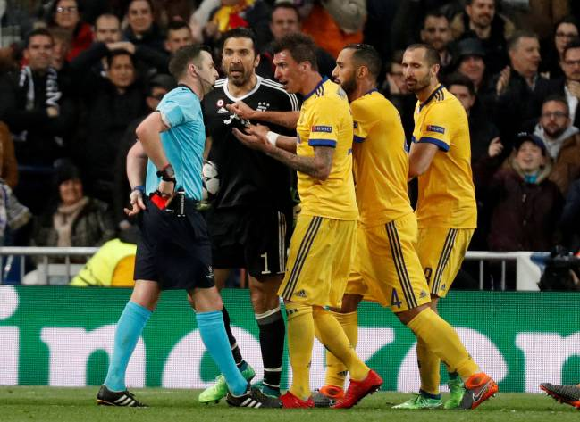 Juventus' Gianluigi Buffon and team mates remonstrate with referee Michael Oliver after he awarded a penalty to Real Madrid.