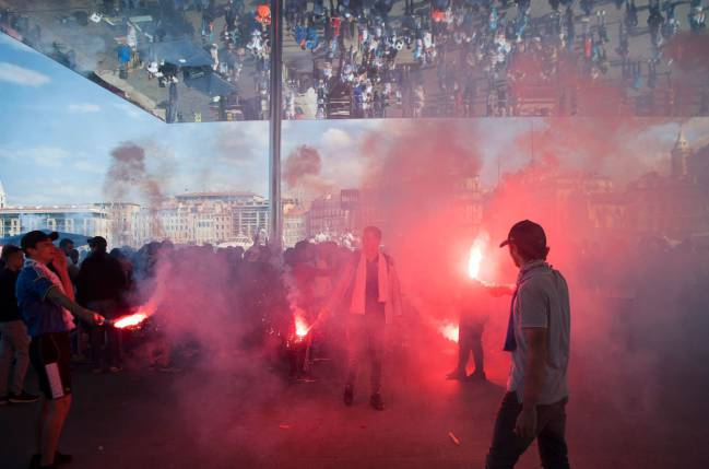 Olympique Marseille supporters let off a flare as they cheer for their team in the Vieux Port in Marseille on May 16, 2018, ahead of the 2018 UEFA Europa Cup Final.