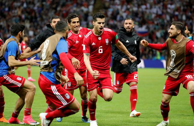 Iran's Saeid Ezatolahi celebrates scoring their first goal with team mates before it was disallowed after a VAR review.