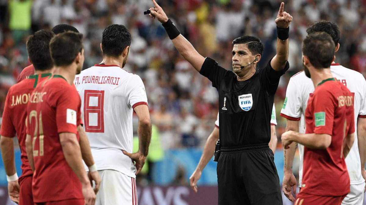 Paraguayan referee Enrique Caceres gestures for VAR during the Russia 2018 World Cup Group B football match between Iran and Portugal