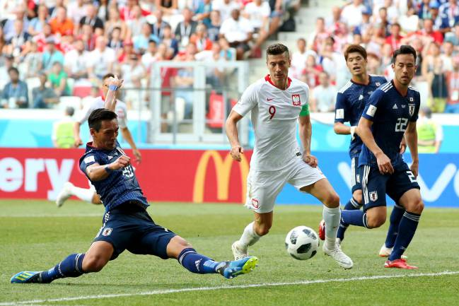 Playing it safe | Tomoaki Makino of Japan clears the ball under pressure from Robert Lewandowski of Poland during the 2018 FIFA World Cup.