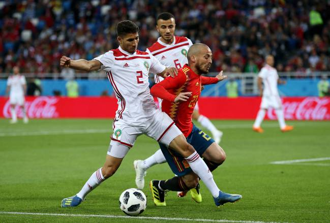 David Silva of Spain is challenged by Achraf Hakimi and Romain Saiss of Morocco during the 2018 FIFA World Cup Russia group B match.