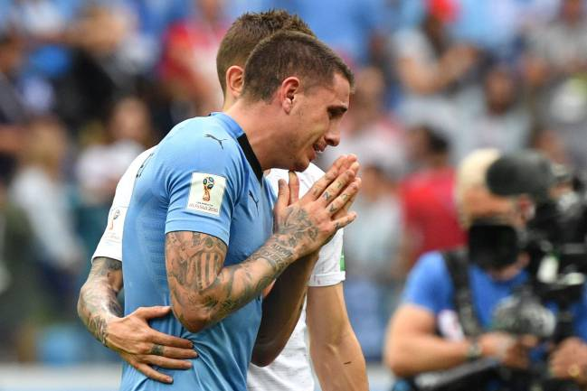 France's defender Lucas Hernandez (back) console Uruguay's defender Jose Gimenez during the Russia 2018 World Cup quarter-final football match between Uruguay and France.