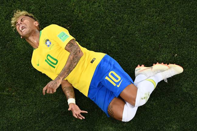 Rolling | Brazil's forward Neymar reacts after beeing tackled by Switzerland's midfielder Valon Behrami at the 2018 World Cup.