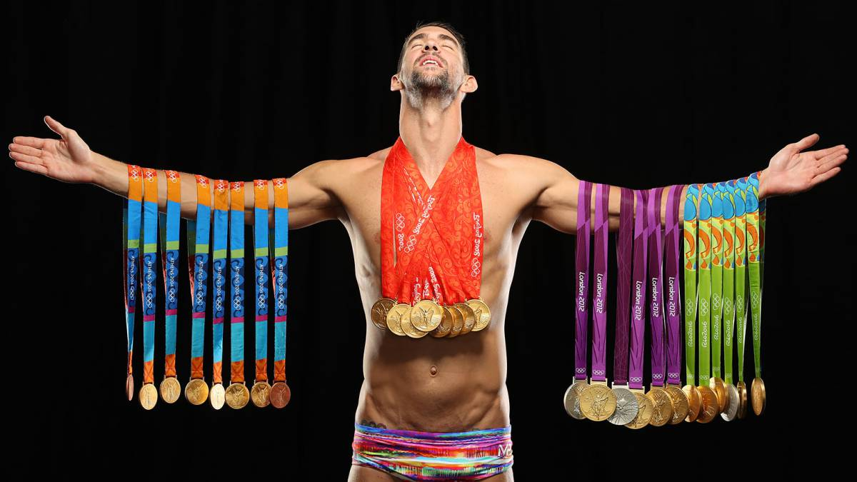 Swimmer Michael Phelps poses with all 28 Olympic medals