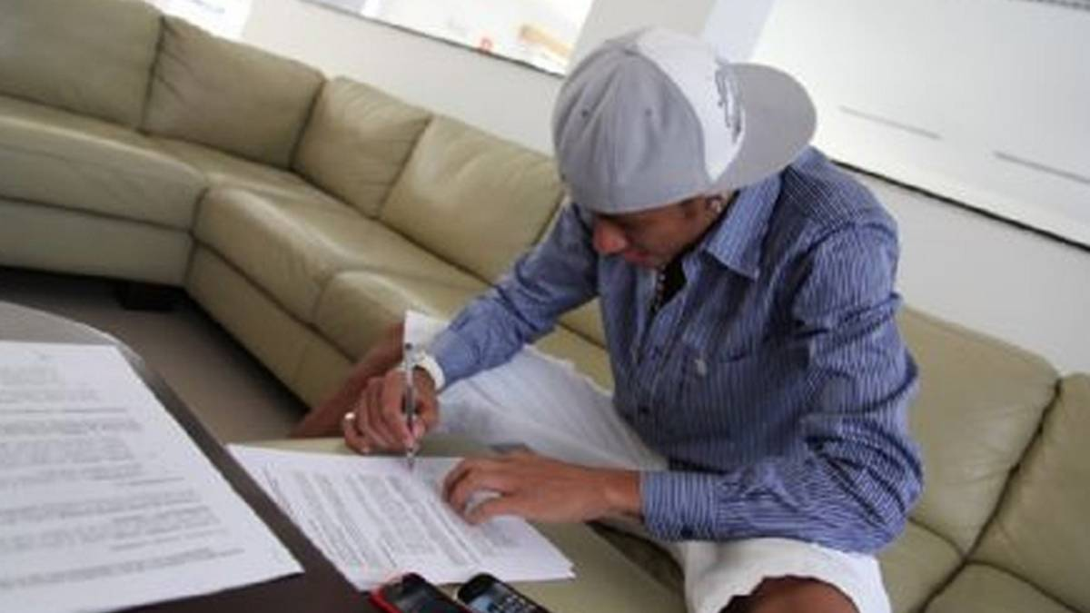 Neymar signs his fanous name onto some paper.