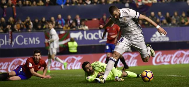 Real Madrid's Karim Benzema, right, duels for the ball with Osasuna's goalkeeper Salvatore Sirigu during the Spanish La Liga soccer match between Real Madrid and Osasuna, at El Sadar stadium, in Pamplona, northern Spain, Saturday, Feb.11.
