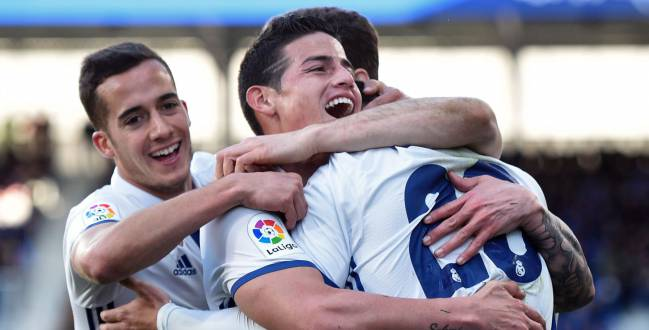 Real Madrid's midfielder Marco Asensio Willemsen (C) celebrates with teammates forward Lucas Vazquez (L) and Colombian midfielder James Rodriguez after scoring his team's fourth goal during the Spanish league football match SD Eibar vs Real Madrid CF at the Ipurua stadium in Eibar on March 4, 2017.