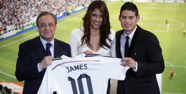 Colombia's soccer player James Rodriguez (R) stands with his wife Daniela and Real Madrid president Florentino Perez (L) as he holds up his new Real Madrid jersey, during a presentation at the Santiago Bernabeu stadium in Madrid, July 22, 2014. Real Madrid have signed Rodriguez from Monaco on a six-year contract, the La Liga club said on Tuesday. The World Cup's Golden Boot winner with six goals, is Real's second major signing of the transfer window after Germany midfielder Toni Kroos from Bayern Munich. No details of the fee for Rodriguez were disclosed but media reports said it was around 80 million euros ($107.9 million).