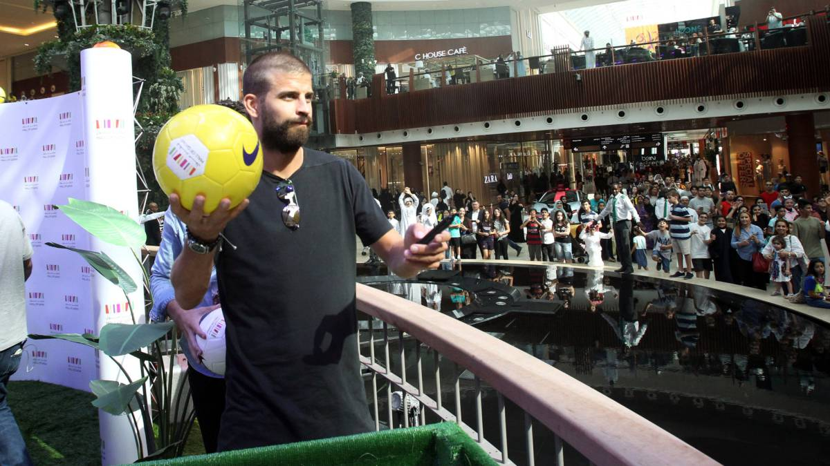 Spain's national team soccer player Gerard Pique signs his autograph on a soccer ball to the fans in a shopping centre in Doha, Qatar, July 5, 2017.