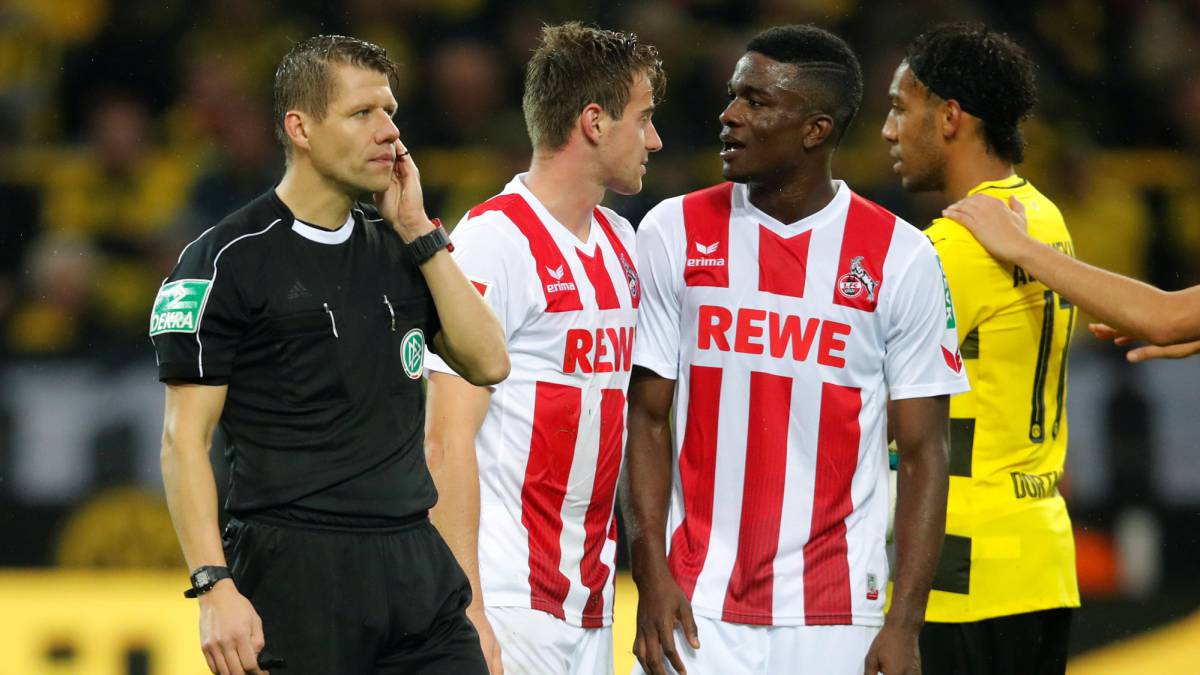 Referee Patrick Ittrich awaits instruction from the VAR to give the penalty to Dortmund against Cologne.
