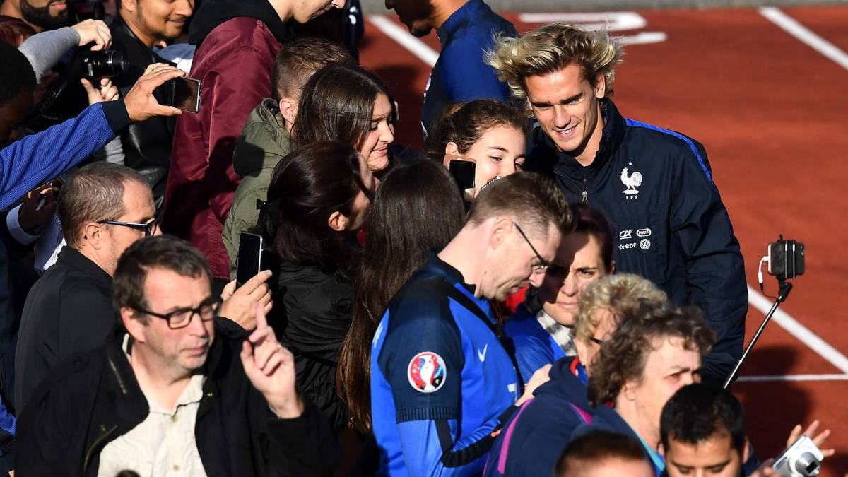 Griezmann posa con aficionados antes del entrenamiento con la selección de Francia.