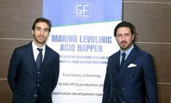 Flamini (izquierda), con el cartel de su empresa de bioquímica.