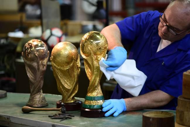 Un artesano de la joyería GDE Bertoni de Milán (Italia) trabaja en la conservación del trofeo de campeón de la Copa Mundial de la FIFA en abril de 2018.