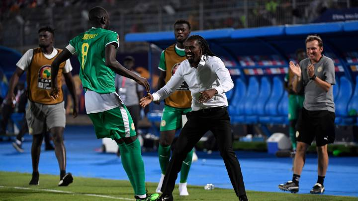 Senegal's defender Cheikhou Kouyate celebrates with his coach Senegal's coach Aliou Cisse after their team scored a goal during the 2019 Africa Cup of Nations (CAN) Semi-final football match between Senegal and Tunisia at the 30 June stadium in Cairo on July 14, 2019. (Photo by Khaled DESOUKI / AFP)